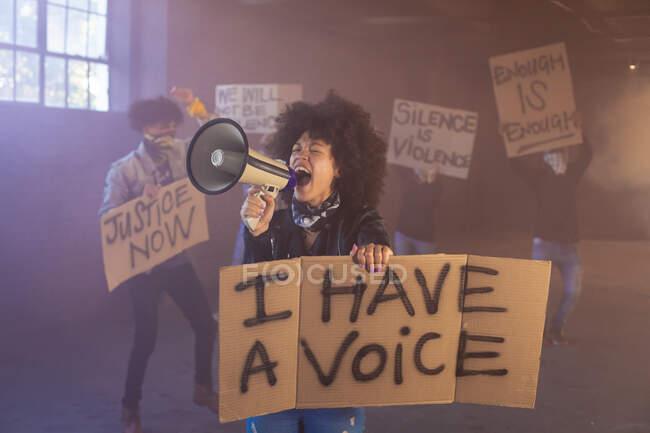 Змішана расова жінка кричить у мегафоні, тримаючи знак протесту. протестуючих на задньому плані. Статева рідина lgbt ідентичність Расова рівність. — стокове фото