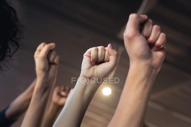 Многонациональная группа людей в масках для лица, поднимающих кулаки. Концепция гендерного расового равенства. — стоковое фото