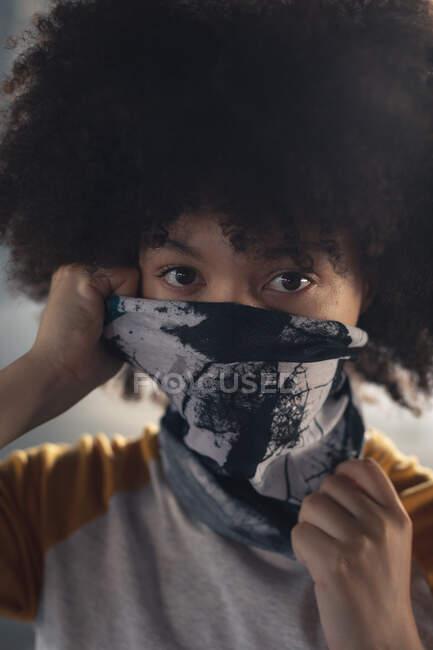 Змішана расова жінка поставила маску обличчя, дивлячись на камеру. Статева рідина lgbt ідентичність Расова рівність. — стокове фото