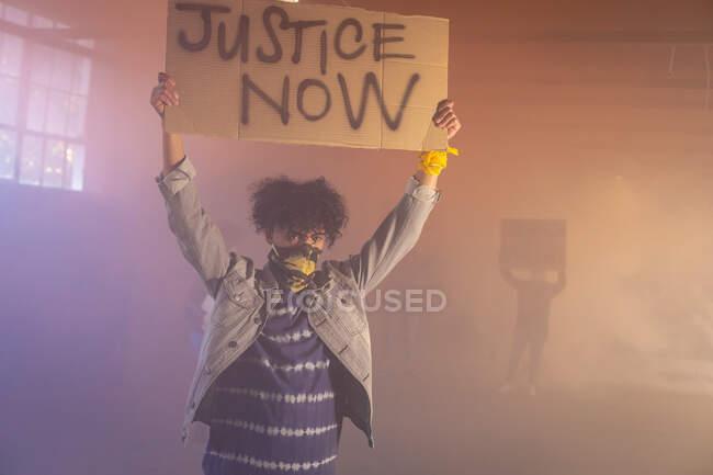 Змішаний расовий чоловік у масці, тримає знак протесту. протестуючих на задньому плані. Статева рідина lgbt ідентичність Расова рівність. — стокове фото