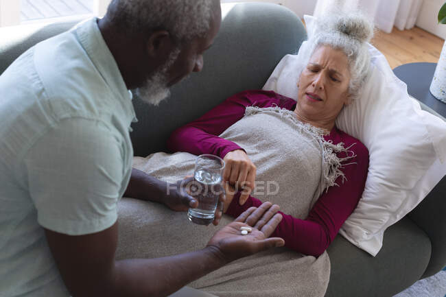 Senior caucasian woman lying sick on couch man passing medicine and water in living room. staying at home in self isolation during quarantine lockdown. — Stock Photo
