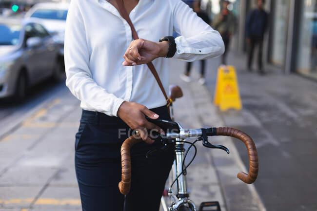 У середній частині афро-американської жінки з перевіркою велосипедів на вулиці. Концепція життя під час коронавірусної ковини 19. — стокове фото