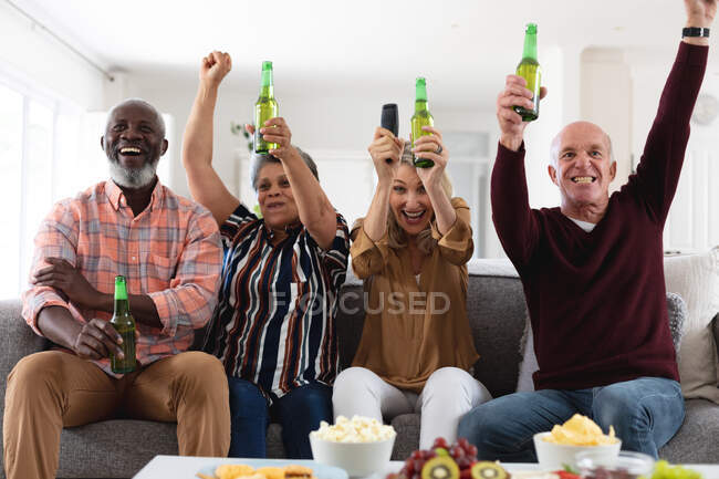 Senior caucasian and african american couples sitting on couch watching game drinking beer at home. senior retirement lifestyle friends socializing. — Stock Photo