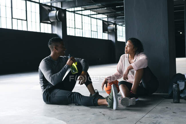 African american man and woman sitting in empty urban building and resting after playing basketball. drinking water and talking. urban fitness healthy lifestyle. — Stock Photo