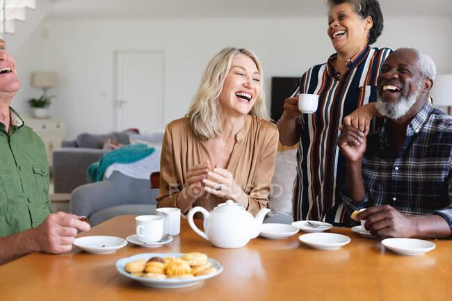 Старші кавказькі та афро-американські пари сидять за столом і п'ють чай удома. Друзі на пенсії.. — стокове фото