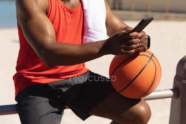 Mittelteil eines fitten afrikanisch-amerikanischen Mannes, der in der Sonne sitzt und Basketball mit dem Smartphone hält. gesunde Ruhestand Technologie Kommunikation Outdoor Fitness Lebensstil. — Stockfoto