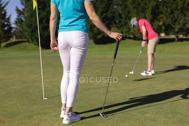 Duas mulheres caucasianas a usar máscaras faciais a jogar golfe uma a pôr no buraco. esporte lazer hobbies golfe saudável ao ar livre estilo de vida higiene durante coronavírus covid 19 pandemia. — Fotografia de Stock