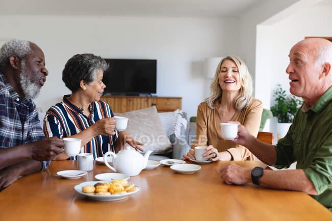 Parejas mayores caucásicas y afroamericanas sentadas junto a la mesa tomando té en casa. senior retiro estilo de vida amigos socializar. - foto de stock