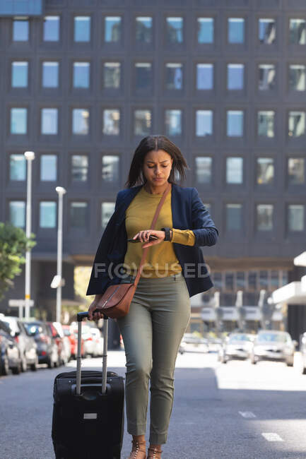 African american woman with trolley bag checking time while walking on the street. lifestyle living during coronavirus covid 19 pandemic. — Stock Photo