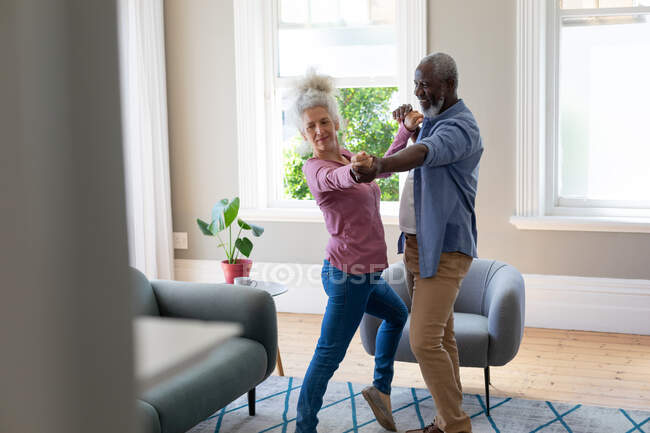Senior mixed race couple dancing in living room. staying at home in self isolation during quarantine lockdown. — Stock Photo