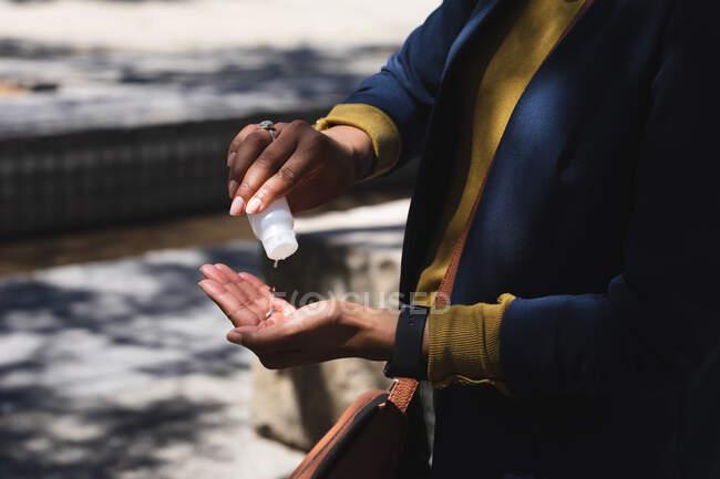 Parte média da mulher afro-americana usando higienizador de mãos na rua. estilo de vida que vive durante o coronavírus covid 19 pandemia. — Fotografia de Stock