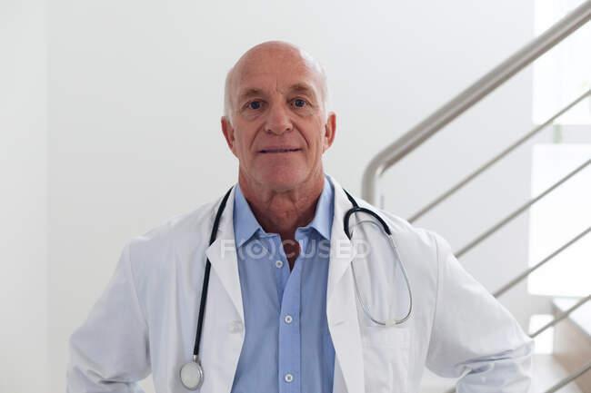 Ritratto di anziano medico maschio caucasico che guarda la telecamera e sorride. operaio medico professionista. — Foto stock