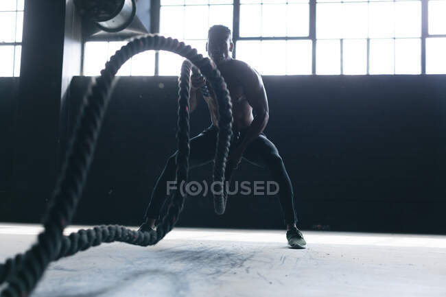 African american man wearing sports clothes battling ropes in empty urban building. urban fitness healthy lifestyle. — Stock Photo