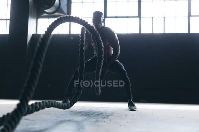 Африканский американец в спортивной одежде сражается на веревках в пустом городском здании. здоровый образ жизни. — стоковое фото