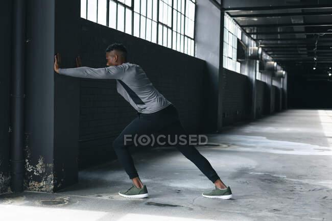 Африканский американец опирается на стену в пустом городском здании и растягивается. здоровый образ жизни. — стоковое фото