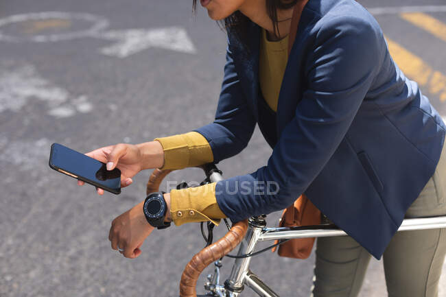 Mulher afro-americana usando smartphone apoiado na bicicleta na rua. estilo de vida que vive durante o coronavírus covid 19 pandemia. — Fotografia de Stock