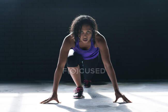 Африканская американка в спортивной одежде, стоящая на коленях в пустом городском здании. здоровый образ жизни. — стоковое фото
