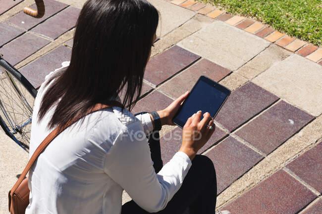 Африканська американка користується цифровим планшетом, сидячи в корпоративному парку. Концепція життя під час коронавірусної ковини 19. — стокове фото