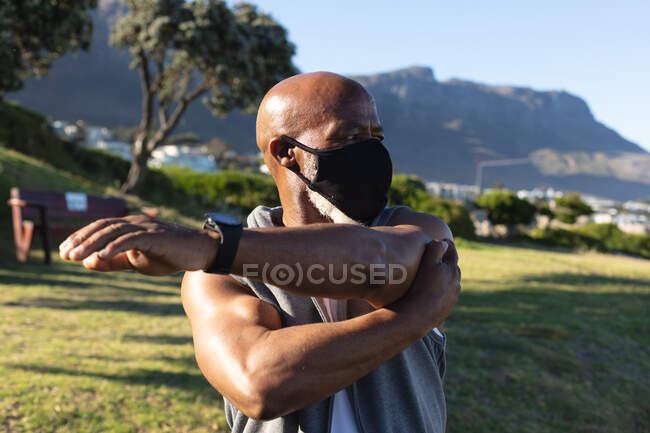 Fitter älterer afrikanisch-amerikanischer Mann mit Gesichtsmaske, der im Freien Stretching übt. gesunder Ruhestand Outdoor-Fitness-Lebensstil Hygiene während Coronavirus covid 19 Pandemie. — Stockfoto