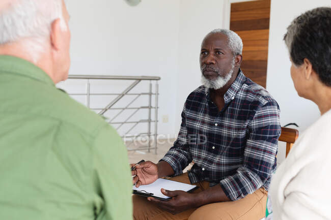 Diverse group of seniors talking during a group therapy session at home. health fitness wellbeing at senior care home. — Stock Photo