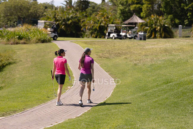 Two caucasian women playing golf walking on path at golf course. sport leisure hobbies golf healthy outdoor lifestyle. — Stock Photo