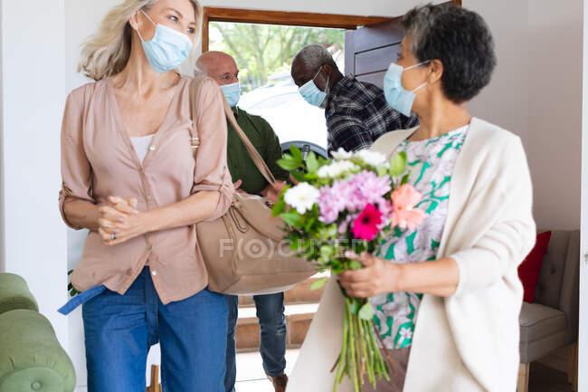 Старшая африканская американская пара здоровается со старшей кавказской парой в масках для лица дома. здоровье гигиены благополучие в доме престарелых во время коронавирусной ковиды 19 пандемии. — стоковое фото