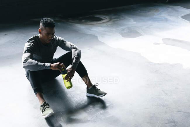 Африканский американец сидит в пустом городском здании и отдыхает после игры в баскетбол. держа бутылку воды. здоровый образ жизни. — стоковое фото