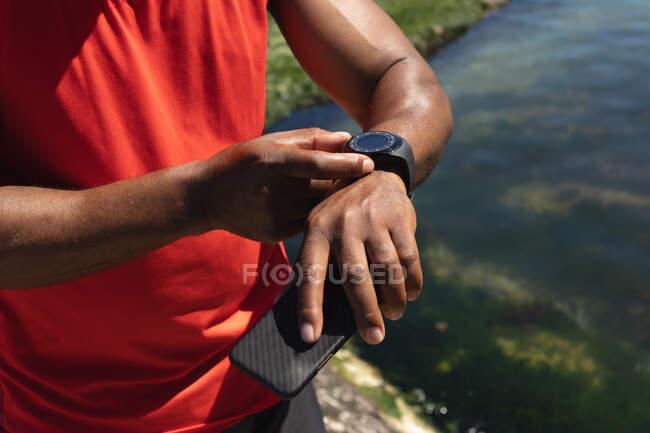 Mittelteil des fitten Mannes beim Training mit der Smartwatch in der Sonne. gesunde Ruhestand Technologie Kommunikation Outdoor Fitness Lebensstil. — Stockfoto