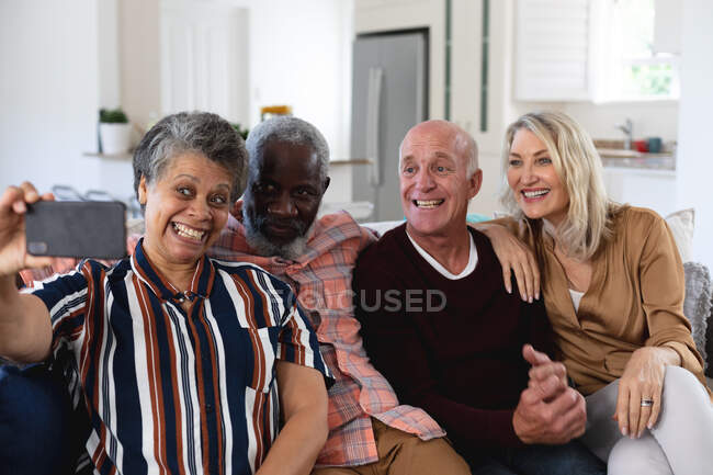 Senior caucasian and african american couples sitting on couch taking a selfie at home. senior retirement lifestyle friends socializing. — Stock Photo