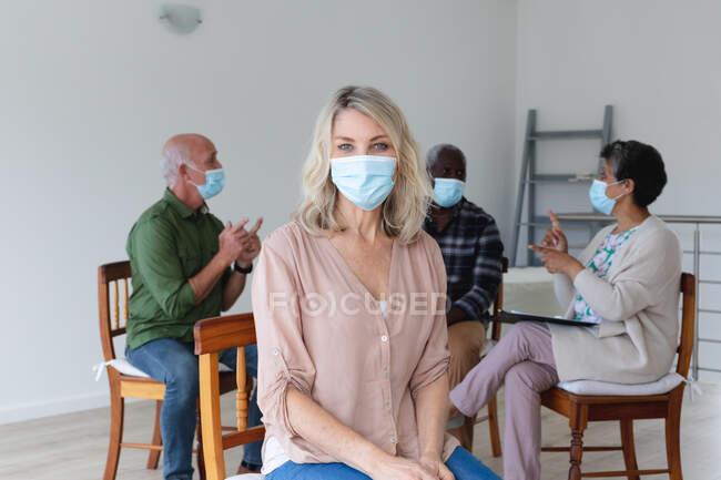 Різні люди похилого віку в масках на обличчі розмовляють під час групового сеансу терапії вдома. Здоров'я гігієни благополуччя в будинку престарілих під час коронавірусу covid 19 пандемії. — стокове фото