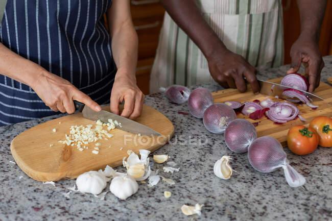 Casal de raça mista em pé em legumes de corte de cozinha. ficar em casa em auto-isolamento durante o confinamento de quarentena. — Fotografia de Stock