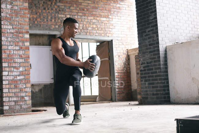 Африканский американец тренируется с мячом в пустом городском здании. здоровый образ жизни. — стоковое фото