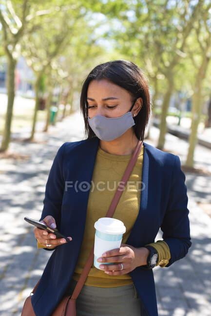 Mujer afroamericana con máscara facial con taza de café usando smartphone en la calle. estilo de vida durante la pandemia de coronavirus covid 19. - foto de stock