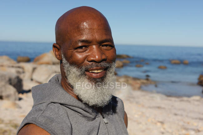 Portrait of fit senior african american man by the sea smiling. healthy retirement outdoor fitness lifestyle. — Stock Photo