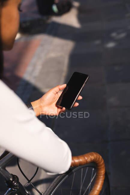 Mulher afro-americana usando smartphone enquanto se inclina na bicicleta na rua. estilo de vida conceito de vida durante coronavírus covid 19 pandemia. — Fotografia de Stock