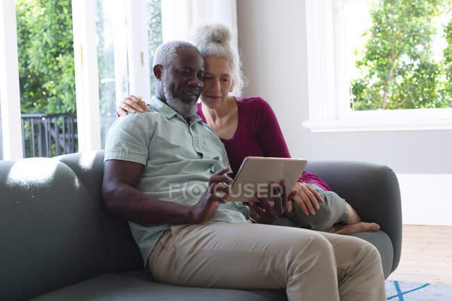 Senioren-Mixed-Race-Paar sitzt auf der Couch und schaut gemeinsam auf das digitale Tablet im Wohnzimmer. Während der Quarantäne zu Hause bleiben und sich selbst isolieren. — Stockfoto