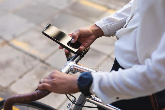 Seção média da mulher afro-americana com bicicleta usando smartphone na rua. estilo de vida conceito de vida durante coronavírus covid 19 pandemia. — Fotografia de Stock