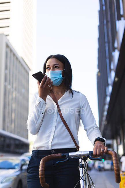 African american woman wearing face mask with bicycle talking on smartphone on the street. lifestyle living concept during coronavirus covid 19 pandemic. — Stock Photo