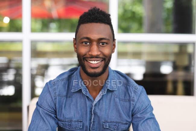 Портрет африканського американця, що сидить у кафе, дивиться на камеру і посміхається. Бізнесмен їде до міста.. — стокове фото