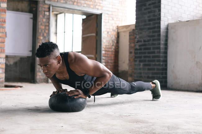 Африканський американський чоловік, який займається фізичними вправами, штовхає м'яч для медикаментів у порожньому міському будинку. Здоровий спосіб життя в місті — стокове фото