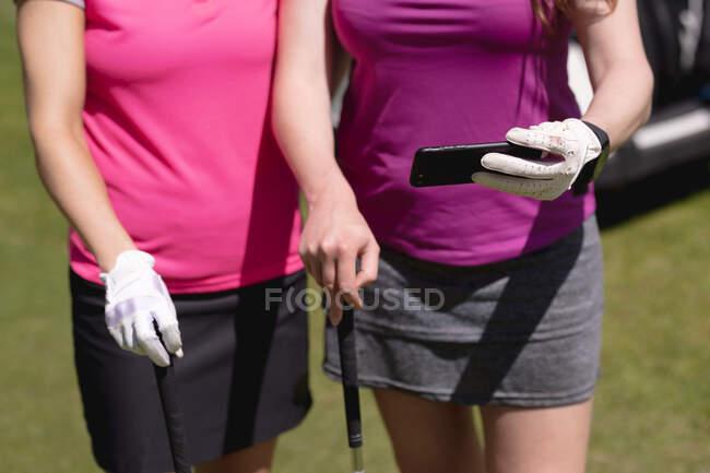 Mitte zwei Frauen, die an einem sonnigen Tag auf dem Golfplatz ihr Smartphone benutzen. Sport und aktiver Lebensstil. — Stockfoto