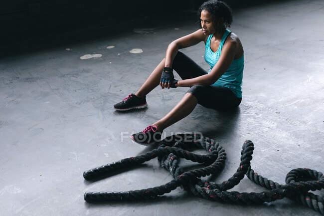 Африканская американка в спортивной одежде отдыхает после борьбы с веревками в пустом городском здании. здоровый образ жизни. — стоковое фото