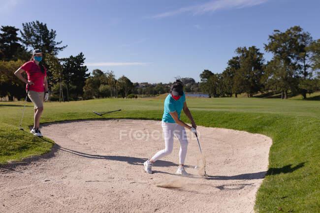 Duas mulheres caucasianas a usar máscaras faciais a jogar golfe, uma a levar um tiro de um bunker. esporte lazer hobbies golfe saudável ao ar livre estilo de vida higiene durante coronavírus covid 19 pandemia. — Fotografia de Stock