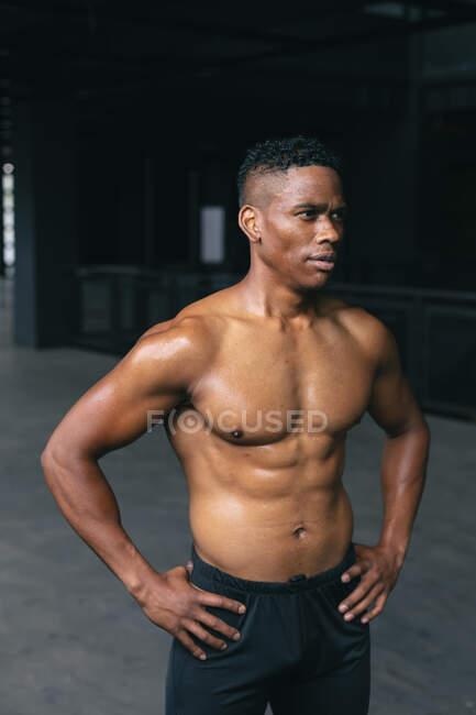 Hombre afroamericano de pie y flexionando sus músculos en un edificio urbano vacío. aptitud urbana estilo de vida saludable. - foto de stock
