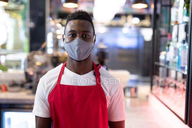 Портрет африканского американского бариста в маске, смотрящего в камеру. здоровье и гигиена в бизнесе во время пандемии коронавируса. — стоковое фото