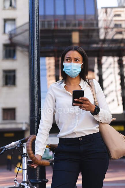 Mulher afro-americana usando máscara facial segurando smartphone e de pé com bicicleta na rua. estilo de vida conceito de vida durante coronavírus covid 19 pandemia. — Fotografia de Stock