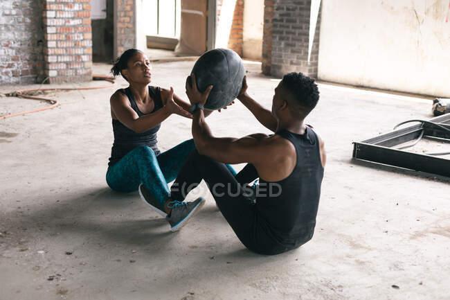 Африканский американец и женщина занимаются спортом с мячом в пустом городском здании. здоровый образ жизни. — стоковое фото