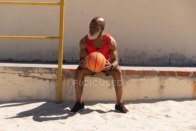 Подходит старший африканский американец, сидящий на ступеньках на солнце, держа баскетбол. здоровый образ жизни на свежем воздухе. — стоковое фото