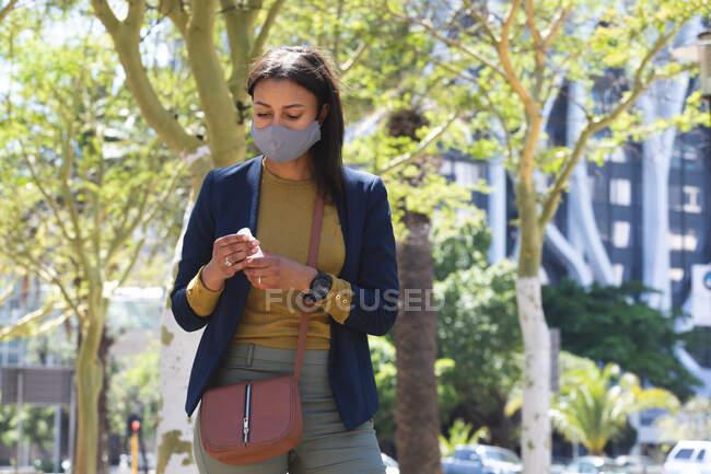 Afroamerikanerin mit Mundschutz hält Händedesinfektionsflasche auf der Straße. Lebensstil während Coronavirus-Covid 19 Pandemie. — Stockfoto