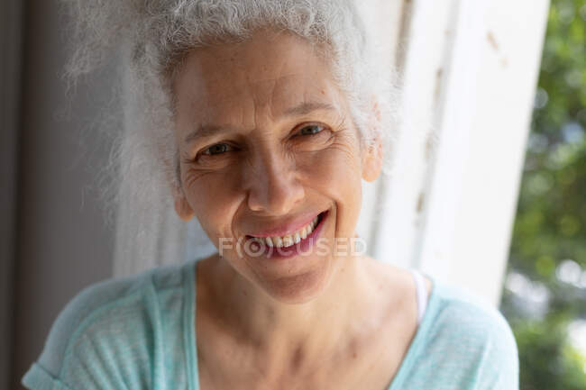 Portrait of senior caucasian woman looking at camera and smiling at home. staying at home in self isolation during quarantine lockdown. — Stock Photo